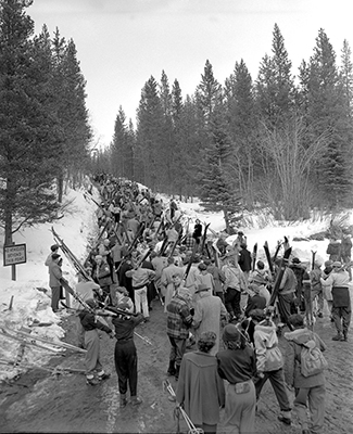 1956-february-skiers-hike-up-hill-at-norquay-wearing-trousers-long-coats-and-caps-image-via-alberta-provincial-archives